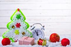Nya Year& x27; s-sammansättning: klocka, julgran och en gåva i Arkivfoton