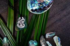 Nya Zeeland - themed objekt för maori - pendan metall och greenstone Arkivbild