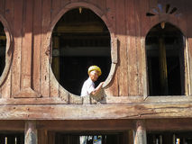 Nyaungshwe, Myanmar - January 24, 2015: An unidentified local ol. D man wearing yellow turban sitting at the unique oval window of Shwe Yaunghwe Kyaung monastery Stock Image