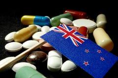 Nyazeeländsk flagga med lotten av medicinska preventivpillerar som isoleras på svartbac Royaltyfri Foto