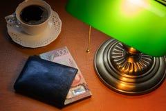 Nyazeeländska dollar, på ett stilfullt skrivbord som tänds med en packa ihop lampa royaltyfri bild