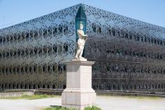 Nybygge som byggs på en modern arkitektur med en främst gammal staty arkivbilder