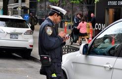 NYC: Полицейский давая штраф за нарушение правил стоянки Стоковые Фото