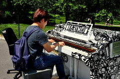 NYC :弹钢琴的年轻人在中央公园 免版税库存照片