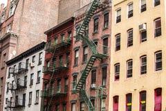与防火梯, NYC,美国的老五颜六色的大厦 库存图片