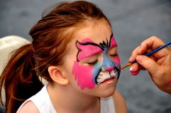 NYC: Artists Face Painting a Little Girl Stock Images