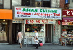 NYC: Asian Restaurant in Chinatown. A Chinese family walks past a small restaurant advertising the cuisines of three Asian countries - China, Japan, and Thailand royalty free stock photography