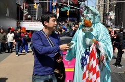 NYC:  Asiatisk turist- tippande staty av Liberty Mime Arkivfoto