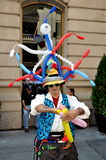 NYC: Balloon Man at French Festival. Balloon artist wearing an original French-inspired red, white, and blue balloon hat fashions animals and other delightful Royalty Free Stock Photos