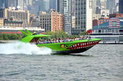 NYC: The Beast Tour Boat. The famous Beast high speed boat zipping along the Hudson River with a full group of tourists passing the Chelsea Piers during a tour stock images