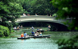 NYC: Central Park's Boating Lake. View of the Central Park's beautiful 1864 Bow Bridge spanning the boating lake filled with people in rental rowboats enjoying Stock Photography