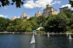 NYC: Central Park Sailboat Pond. Radio-controlled sailboats dot the charming Conservatory Water pond in NYC's Central Park with the luxury apartment buildings on Stock Images