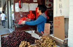 NYC: Chinese Woman Selling Fruit. Woman weighing a customer's purchase of fresh cherries at her small fruit stand on Canal Street in NYC's Chinatown stock image