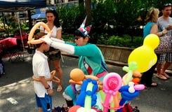 NYC:Clown Making Balloon Hats at Street Fair Stock Photography