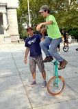NYC: Coach Aiding Unicycle Rider. Coach lends a helping hand to a young man riding his unicycle at the 2011 NYC Unicycle Festival held in the plaza in front of Royalty Free Stock Photo