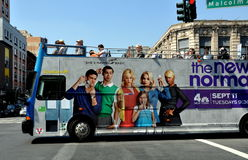 NYC: Double-decker Tourist Bus in Harlem. A double decker tourist bus with an open upper level, its side advertising a new NBC-TV sitcom, on Malcom X Boulevard Royalty Free Stock Photos