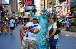 NYC: Family Posing with Statue of Liberty Mime. A family visiting from Asia poses for photos with one of the many Statue of Liberty Mimes in busy NYC's Times Royalty Free Stock Photo