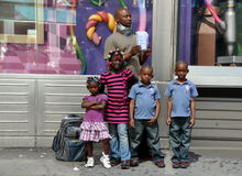 NYC: Family Seeking Donations in Times Square. Father with his four children in the heart of NYC's Times Square holds a sign asking for help and food because he Royalty Free Stock Image