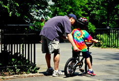 NYC:  Father Teaching Son to Ride Bicycle Royalty Free Stock Photography