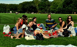 NYC: Friends having picnic in Central Park. A group of friends enjoying a picnic lunch on the velvety green grass at the Great Lawn in New York City's Central Royalty Free Stock Images