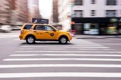 NYC-Gelb-Fahrerhaus, das über Schnitt beschleunigt Stockbild
