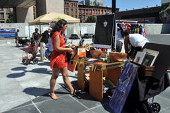NYC: Harlem Flea Market. Woman checks out bric-a-brac being sold by flea market vendor at the Tuesday outdoor market in Adam Clayton Powell, Jr. plaza in NYC's Royalty Free Stock Photos