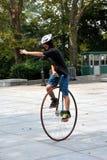 NYC: Junger Mann, der einen Unicycle reitet Stockbild