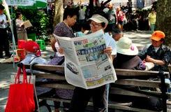 NYC: Läs- kinesisk tidning för kvinna Arkivbild