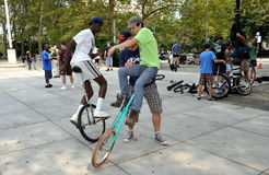 NYC: Learing to Ride a Unicycle. Coach helps a young man to mount his unicycle at the 2011 NYC Unicycle Festival held in the plaza in front of Grant's Tomb Stock Photos