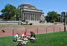NYC: Library at Columbia University. Three women students enjoy a picnic on the grassy lawn in front of the great Library of Columbia University in New York City Royalty Free Stock Photography