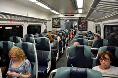 NYC: LIRR Commuter Train with Passengers. Interior of a modern Long Island Railroad commuter train filled with passengers enroute from Pennsylvania Station to Stock Photo