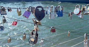 NYC Love Locks on boardwalk wires by the Brooklyn Bridge. Romantic love themed red, violet, silver and brass padlocks are clipped to criss-crossed wires on the Royalty Free Stock Image