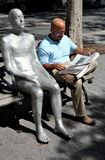 NYC: Man Reading Newspaper & Sculpture. Man reading a newspaper seated next to an outdoor sculpture of a nude silver man in Dag Hammersjold Park on East 44th royalty free stock image