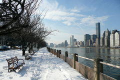 NYC: Manhattan from Roosevelt Island. Manhattan in winter across East River from Roosevelt Island, with snowy path Stock Image