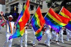 NYC: Manifestantes que levam bandeiras do arco-íris em Pride Parade alegre fotografia de stock royalty free