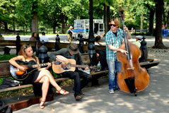 NYC: Musicians in Central Park. A trio of musicians playing guitars and a bass fiddle entertain passerby on the Mall in New York City's Central Park Stock Photo