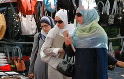 NYC: Muslim Women in Astoria, Queens. Three Muslim women wearing traditional headress scarfs and robes visiting an outdoor street festival on Steinway Street in Royalty Free Stock Photography