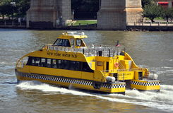 NYC: New York Water Taxi on East River. A yellow New York Water Taxi heading north on the East River passes by the massive stone pylons of the Queensboro (59th Stock Photo