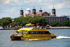 NYC: NY Water Taxi and Ellis Island. A bright yellow New York Water Taxi on the Hudson River passes the historic Ellis Island National Historic Park in New York Royalty Free Stock Photo