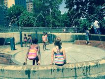 NYC park. Young girls playing at water sprinklers on summer Royalty Free Stock Image