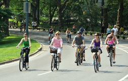 NYC: People Biking in Central Park. Family members enjoying a bicycle ride along the inner park drive in Central Park on a sunny Saturday afternoon in New York Stock Image