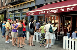 NYC: People Waiting Outside Restaurant for a Table. People queue in line to eat Sunday brunch at the very popular Good Enough to Eat restaurant on Amsterdam Royalty Free Stock Images