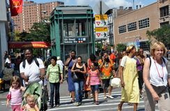 NYC:  People on West 125th Street. A mélange of Whites, Blacks, and Latins walking past the West 125th Street subway station in New York City's Harlem Royalty Free Stock Photography