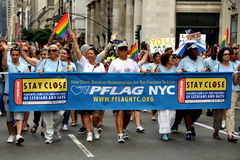 NYC: PFLAG Group at Gay Pride Parade. The New York PFLAG (Parents and Friends of Lesbians and Gays) support group marching behind their banner at the 2011 Gay Stock Images