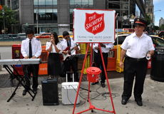 NYC:  Salvation Army Band. Members of the Salvation Army band entertain passerby at NYC's Columbus Circle while the captain rings his bell next to a customary Stock Photography