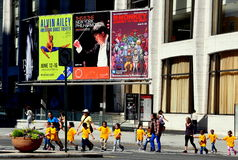 NYC: School Children Crossing Street. Teachers lead a group of young students wearing yellow tee-shirts across the street in front of Avery Fisher Hall at stock images