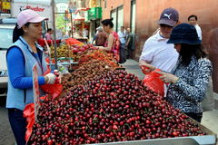 NYC: Selling Cherries in Chinatown. A woman selling fresh, sweet cherries near Canal Street in New York City's bustling Chinatown district royalty free stock images
