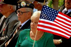 NYC:  Senior Citizens at Memorial Day Service. Senior citizen veteran wearing his decorated hat sits with his wife who holds an American flag during Memorial Day Royalty Free Stock Image