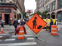 NYC Signs, Men At Work Sign, Manhattan, NYC, NY, USA. A sign at the intersection of 8th Avenue and West 49th Street in Manhattan alerts drivers of work in the Royalty Free Stock Images