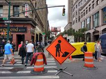 NYC Signs, Men At Work Sign, Manhattan, NYC, NY, USA. A sign at the intersection of 8th Avenue and West 49th Street in Manhattan alerts drivers of work in the Royalty Free Stock Photography